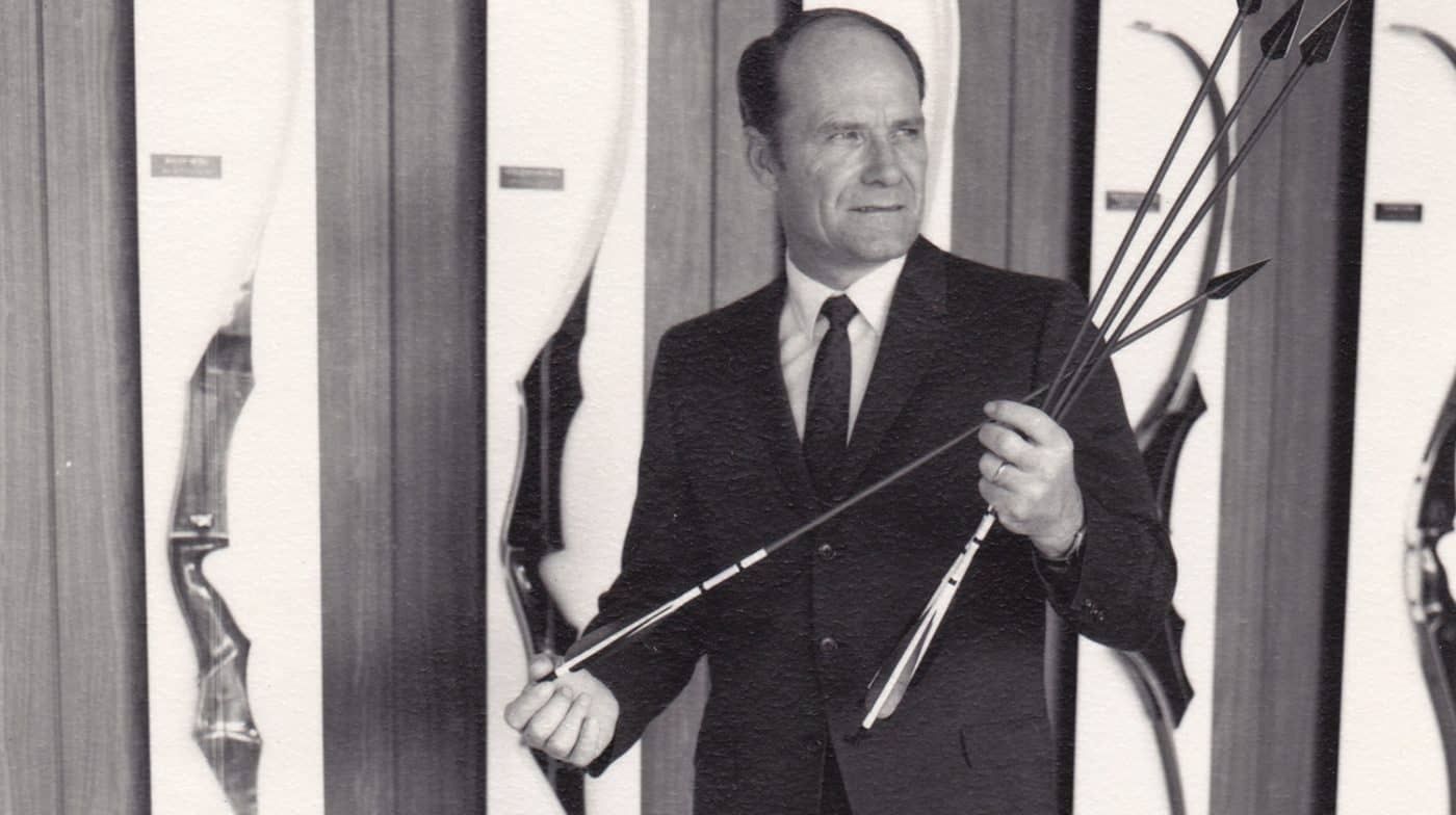 Still photo of Bob Lee standing in front of a Wing Archery bow display in 1972