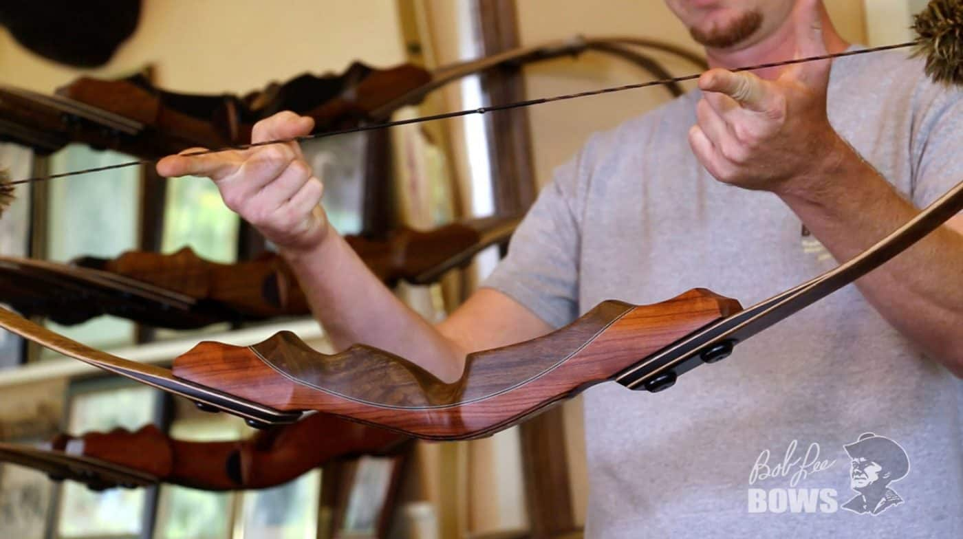 Photo of JJ at Bob Lee Bows showing one way to store a wooden recurve bow